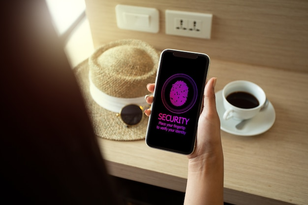 Vrouw op vakantie die smartphone gebruikt om een wachtwoord met vingertop te ondertekenen. mobiel veiligheidsconcept.