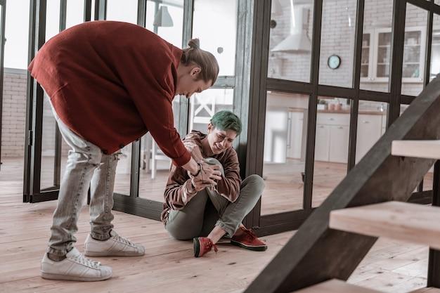 Vrouw op verdieping. groenharige vrouw zittend op de vloer en huilend vechtend met haar agressieve man