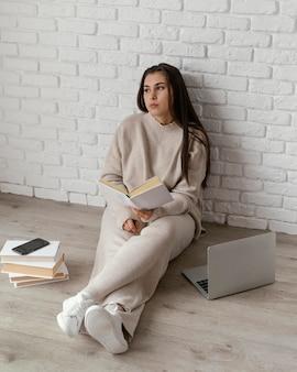 Vrouw op verdieping met boek en laptop