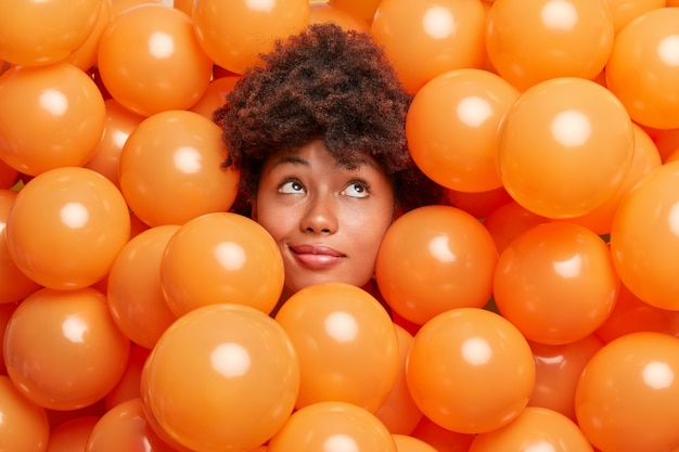 Vrouw op verjaardagsfeestje omringd met kleine oranje ballonnen