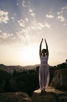 Vrouw op yoga poseren met handen omhoog