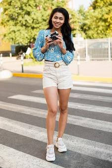 Vrouw op zebrapad die een retro camera met behulp van