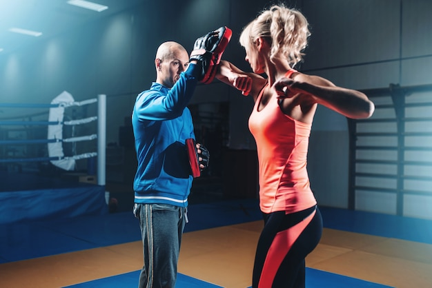 Vrouw op zelfverdedigingstraining met mannelijke trainer, vechttraining in de sportschool, krijgskunst