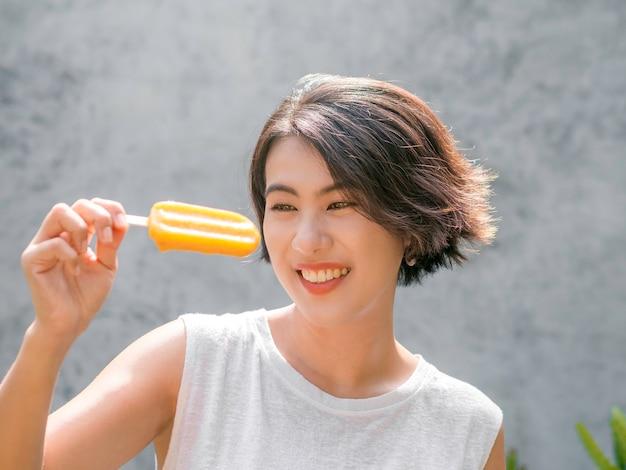 Vrouw op zoek ijslollys. gelukkige mooie aziatische vrouw die een toevallig wit mouwloos overhemd draagt dat gele ijslolly houdt, in openlucht. glimlachend vrouwtje genieten van ijslolly in de zomer.
