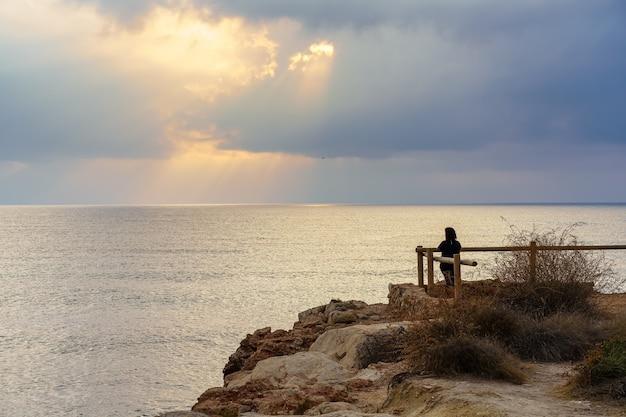 Vrouw op zoek naar de horizon vanuit een gezichtspunt bij gouden zonsondergang boven de zee.