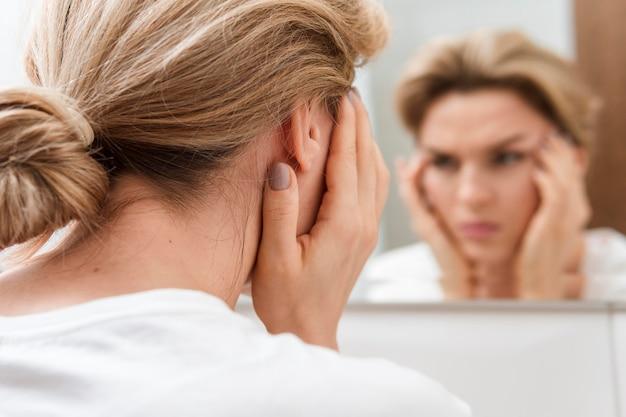 Vrouw op zoek naar de spiegel wazig reflectie