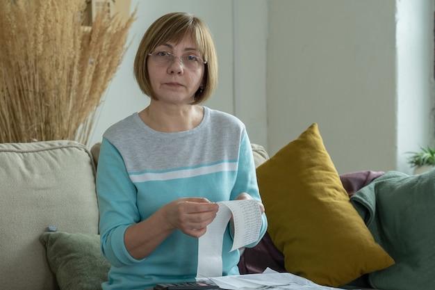 Vrouw op zoek naar een cheque van een supermarktuitgaven bijhouden en budgetteren