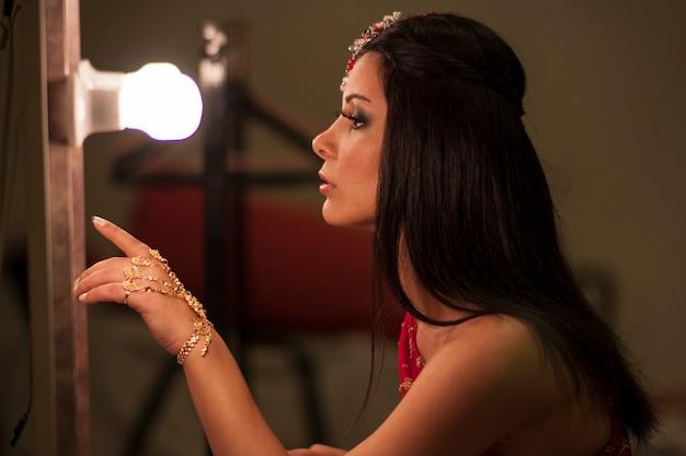 Vrouw op zoek naar een spiegel met een gloeilamp