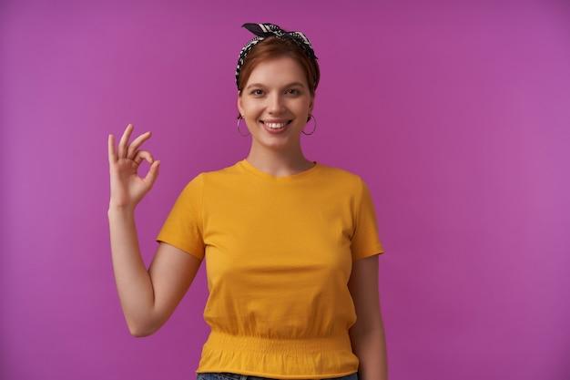 Vrouw op zoek naar jou gekleed in stijlvolle zomer gele t-shirt en zwarte bandana emotie blij blij oke vingers poseren geïsoleerd op paars