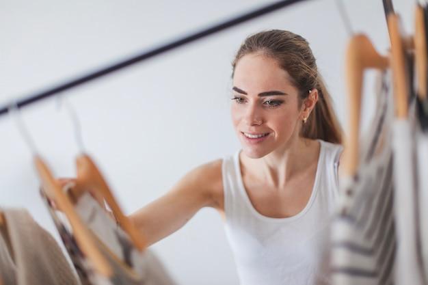 Vrouw op zoek naar kleding in kledingkast