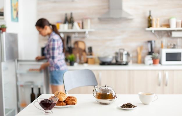 Vrouw op zoek naar koelkast voor voedsel om ontbijt te bereiden in de keuken