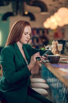 Vrouw op zoek naar smartphone in café