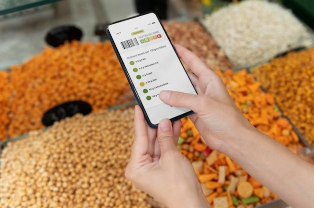 Vrouw op zoek naar verschillende goodies op haar boodschappenlijstje op een smartphone