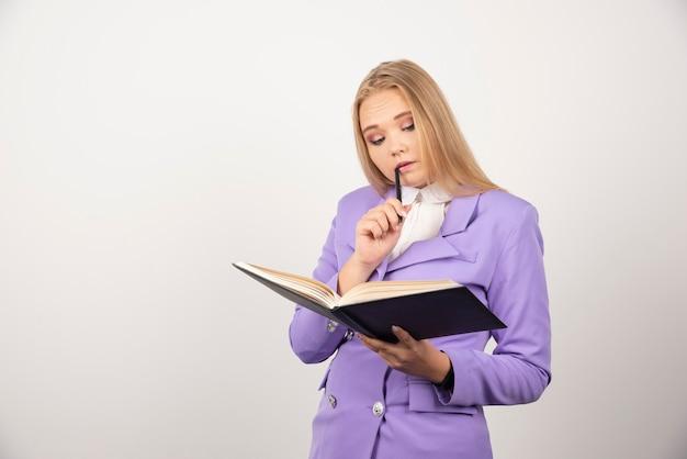 Vrouw op zoek op geopende tablet met potlood op wit.