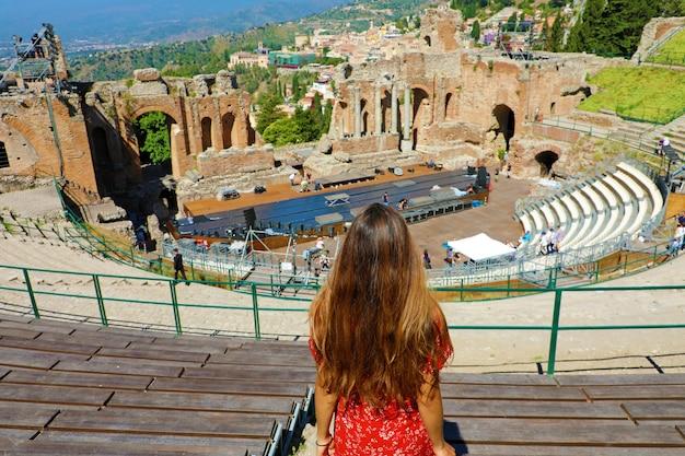 Vrouw op zoek ruïnes van het oude griekse theater in taormina, sicilië italië