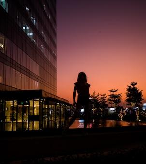 vrouw op zonsondergang in de buurt van gebouw