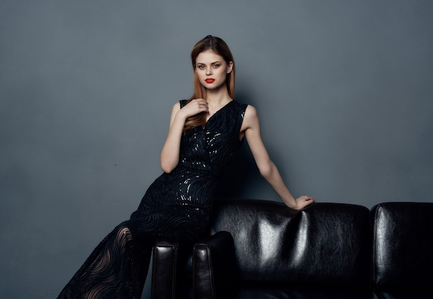 Vrouw op zwarte avondjurk zittend op de bank