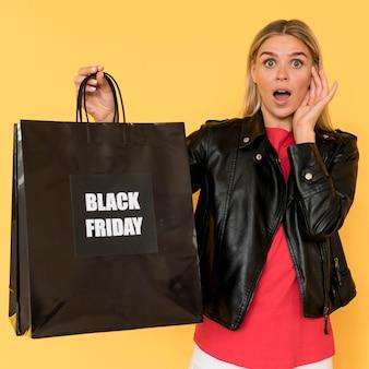 Vrouw op zwarte vrijdagverkoop en grote boodschappentas
