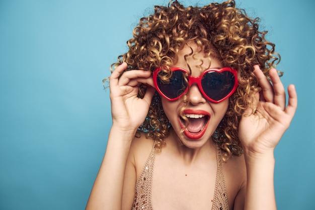 Vrouw open mond zonnebril krullen studio emoties lippenstift blauw