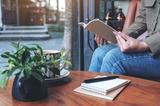 Vrouw openen van een boek met laptops en koffiekopje op houten tafel in café