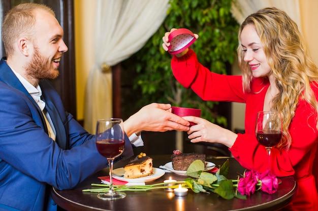 Vrouw opening geschenkdoos aan tafel