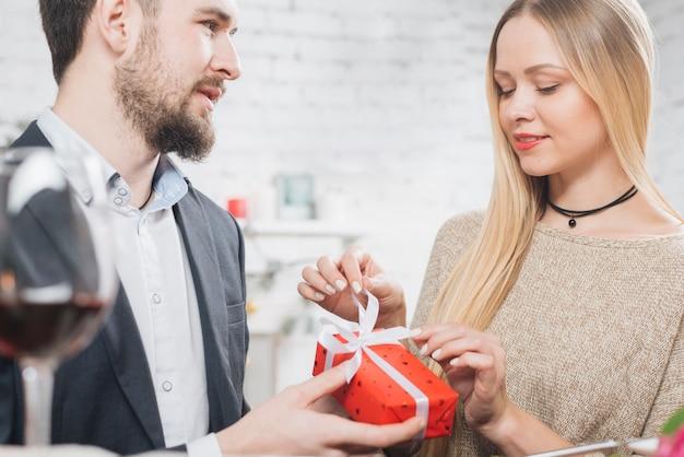 Vrouw opening geschenkdoos van vriendje