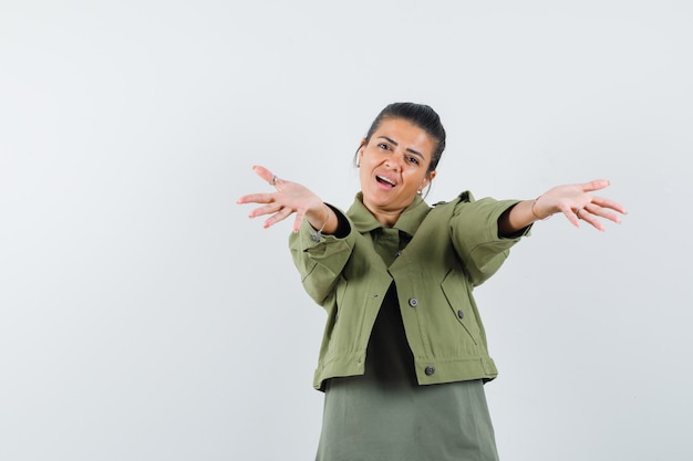 Vrouw opent armen voor knuffel in jas, t-shirt en ziet er mooi uit.