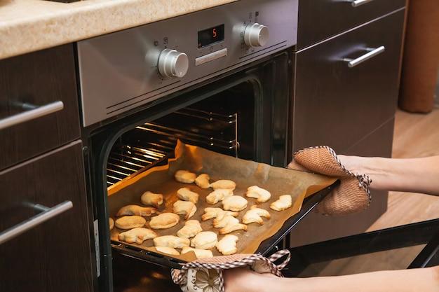 Vrouw opent de oven waar koekjes worden gebakken voor halloween.