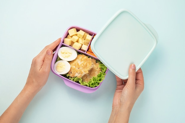 Vrouw opent een plastic lunchbox met lunch. blauwe achtergrond