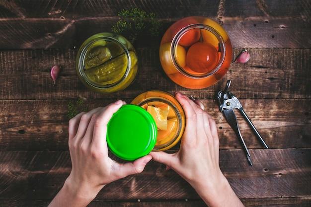 Vrouw opent een pot met zelfgemaakte, verse augurken. groenten in het zuur van verse komkommers, sappige tomaten, zoete courgette.