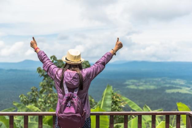 Vrouw opgeheven wapen met duim omhoog op de berg, achtermening, aard reizend concept.