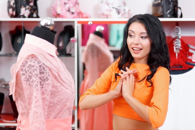Vrouw opgewonden te kijken naar een roze jurk