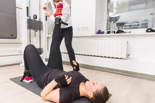 Vrouw opleiding benen op kabel crossover machine