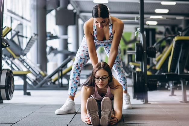 Vrouw opleiding bij gymnastiek met vrouwelijke geschiktheidstrainer