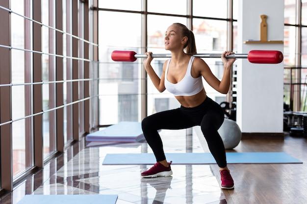 Vrouw opleiding in gymnastiek met bar