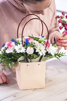 Vrouw oppakken van boeket van verschillende bloemen in papieren cadeauzakje met handvatten. verticaal