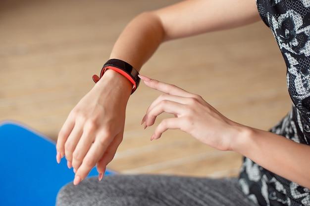 Vrouw opzetten van het fitness slimme horloge voor hardlopen. sportvrouw horloge apparaat controleren.