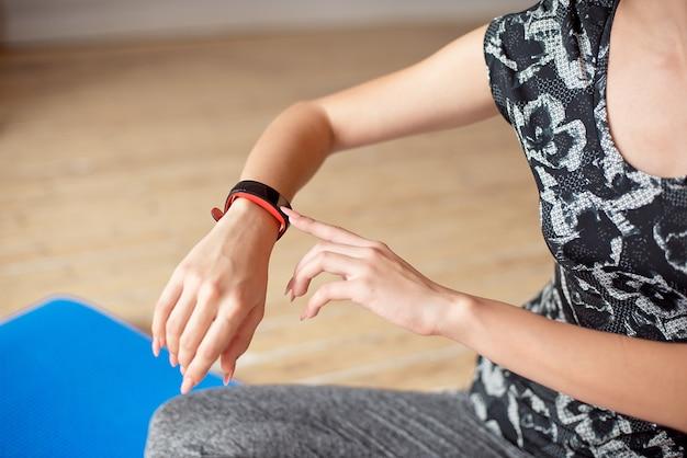 Vrouw opzetten van het fitness slimme horloge voor hardlopen.