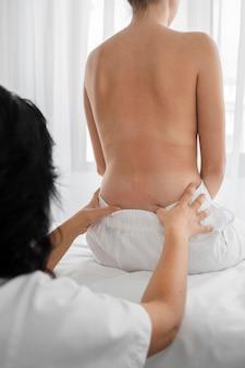 Vrouw osteopaat behandeling van een meisje in het ziekenhuis