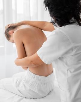 Vrouw osteopaat die een meisje behandelt