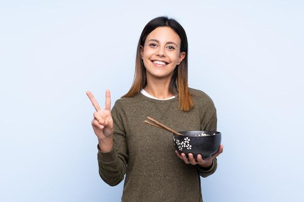 Vrouw over blauwe muur die en overwinningsteken glimlacht toont terwijl het houden van een kom noedels met eetstokjes