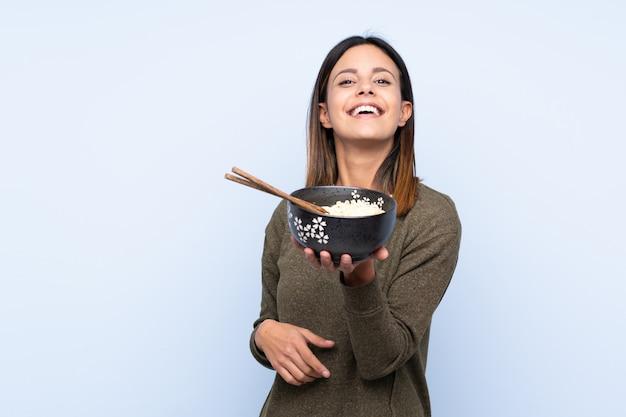 Vrouw over blauwe muur met gelukkige uitdrukking terwijl het houden van een kom van noedels met stokjes