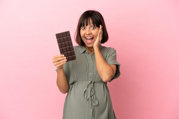Vrouw over geïsoleerde achtergrond zwanger en houdt chocolade vast met verbaasde uitdrukking