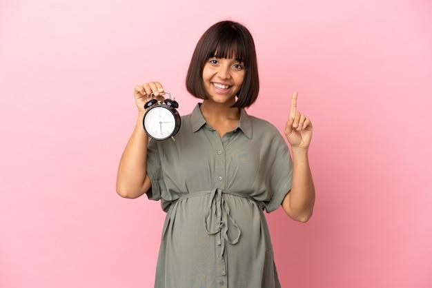 Vrouw over geïsoleerde achtergrond zwanger en houdt de klok vast terwijl ze er één telt