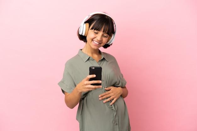 Vrouw over geïsoleerde achtergrond zwanger en muziek luisteren met een mobiel