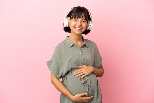 Vrouw over geïsoleerde achtergrond zwanger en muziek luisteren