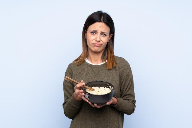 Vrouw over geïsoleerde blauwe muur met droevige uitdrukking terwijl het houden van een kom van noedels met eetstokjes