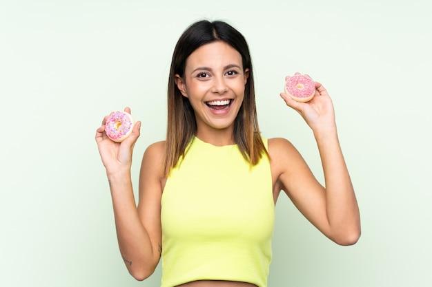 Vrouw over geïsoleerde groene muurholding donuts met gelukkige uitdrukking
