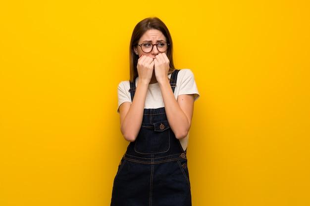 Vrouw over gele muur nerveuze en doen schrikkende het zetten van handen aan mond