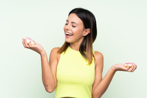 Vrouw over groene muurholding donuts met gelukkige uitdrukking